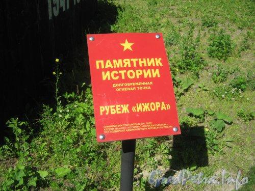 ДОТ «Рубеж «Ижора» » с нечётной стороны Кронштадтской ул. возле пересечения с Корабельной ул. Информационная табличка. Фото 13 июня 2012 г.