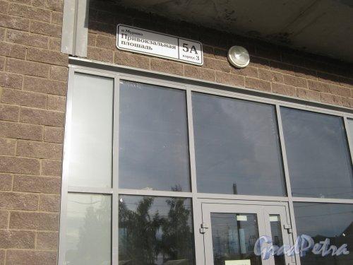 Лен. обл., Всеволожский р-н, пос. Мурино, Привокзальная пл., дом 5а, корпус 3. Фрагмент нижней части фасада здания и табличка с номером дома. Фото 3 июля 2012 г.